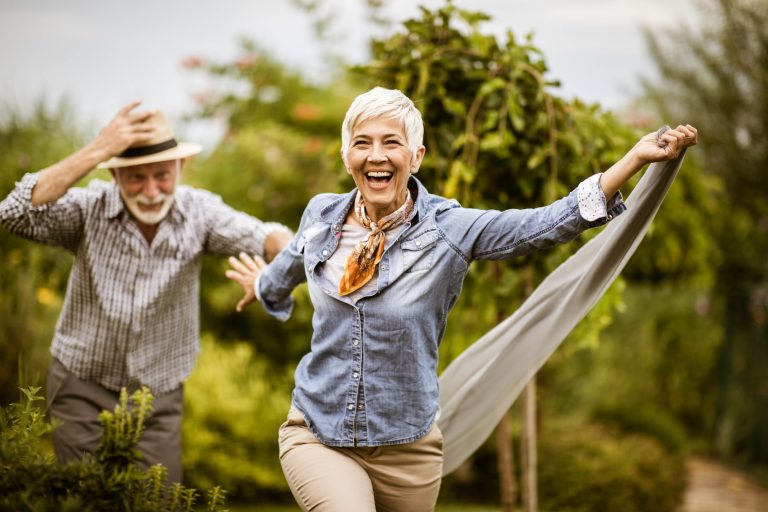 Elder man and woman running in lush green orchard