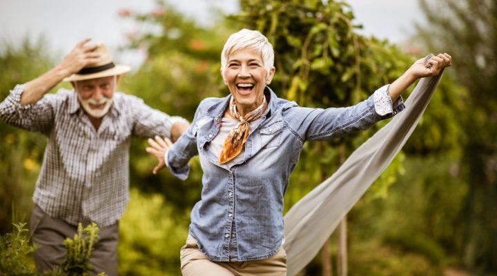 Homme et femme âgés courant dans un verger luxuriant